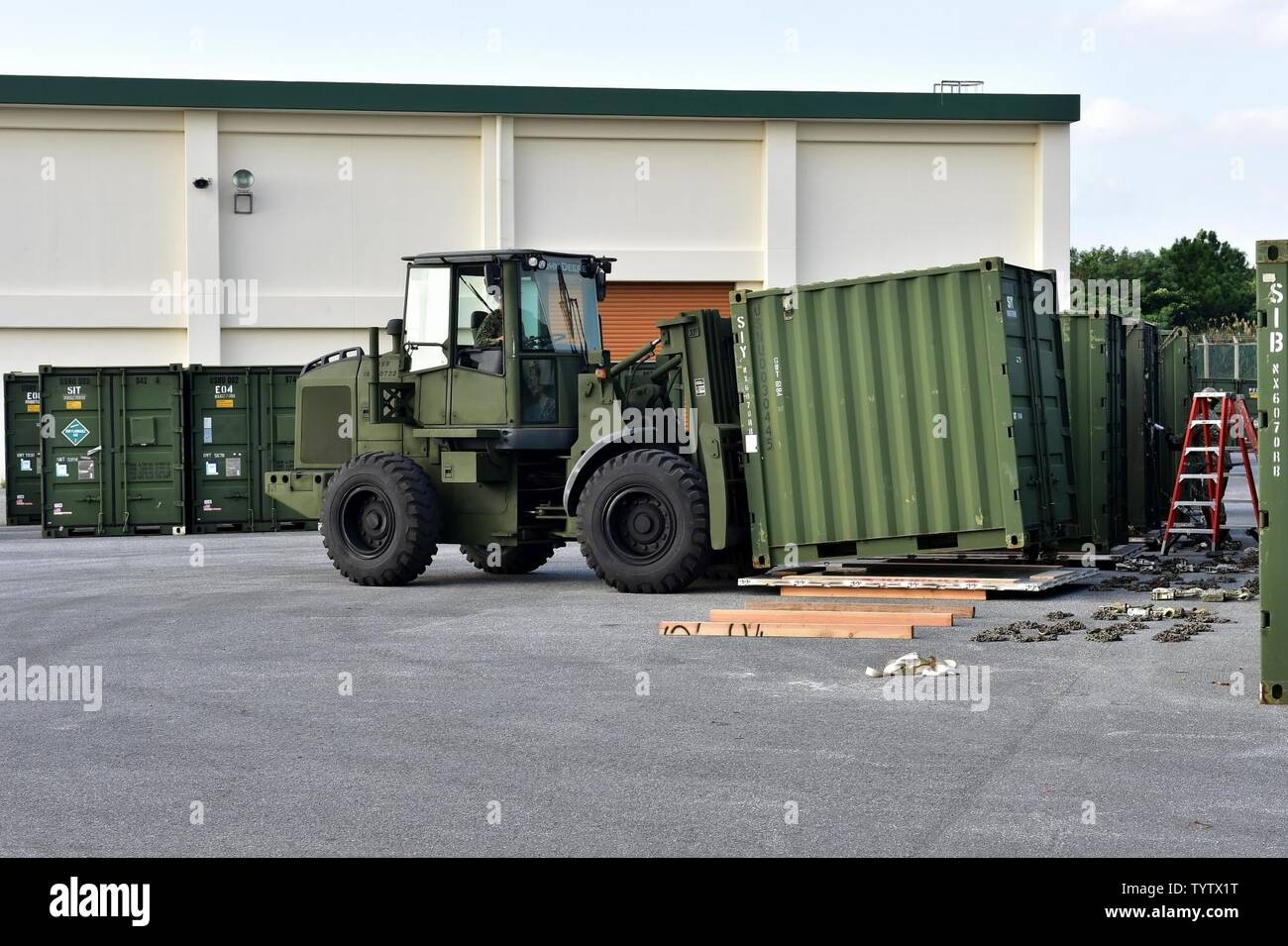 OKINAWA, Japan (Nov. 29, 2016) Seaman Miranda Roudabush, assigned to Naval Mobile Construction Battalion (NMCB) 5, drives a forklift while moving containers onto pallets outside of a warehouse on Camp Shields during an embark exercise. The exercise tests the commands ability to mobilize within 48 hours to react to different types of contingency operations around the world. NMCB 5 is the forward deployed Western Pacific NMCB ready to support Major Combat Operations, Humanitarian Assistance and Disaster Relief operations, and to provide general engineering and civil support to Navy, Marine Corps - Stock Image