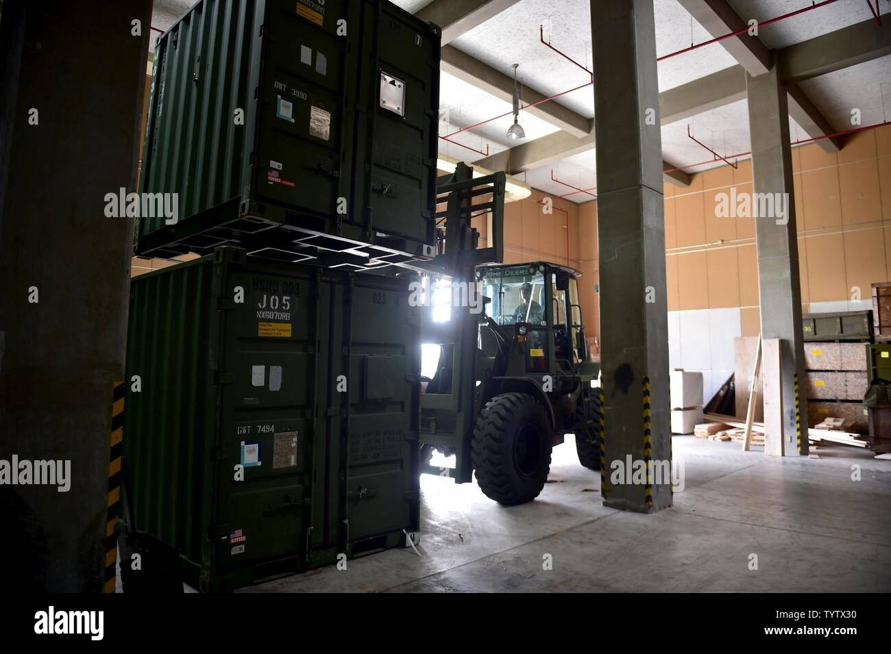 OKINAWA, Japan (Nov. 29, 2016) Seaman Miranda Roudabush, assigned to Naval Mobile Construction Battalion (NMCB) 5, drives a forklift while moving containers inside of a warehouse on Camp Shields during an embark exercise. The exercise tests the commands ability to mobilize within 48 hours to react to different types of contingency operations around the world. NMCB 5 is the forward deployed Western Pacific NMCB ready to support Major Combat Operations, Humanitarian Assistance and Disaster Relief operations, and to provide general engineering and civil support to Navy, Marine Corps and joint ope - Stock Image