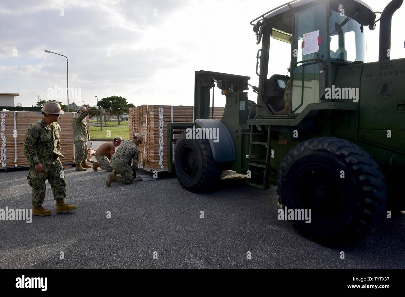 OKINAWA, Japan (Nov. 29, 2016) Petty Officer 2nd Class Bernard Barbuto, a Seabee assigned to Naval Mobile Construction Battalion (NMCB) 5, gives directions to a forklift operator while weighing a pallet on Camp Shields during an embark exercise. The exercise tests the command ability to mobilize within 48 hours to react to different types of types of contingency operations around the world. NMCB 5 is the forward deployed Western Pacific NMCB ready to support Major Combat Operations, Humanitarian Assistance and Disaster Relief operations, and to provide general engineering and civil support to - Stock Image