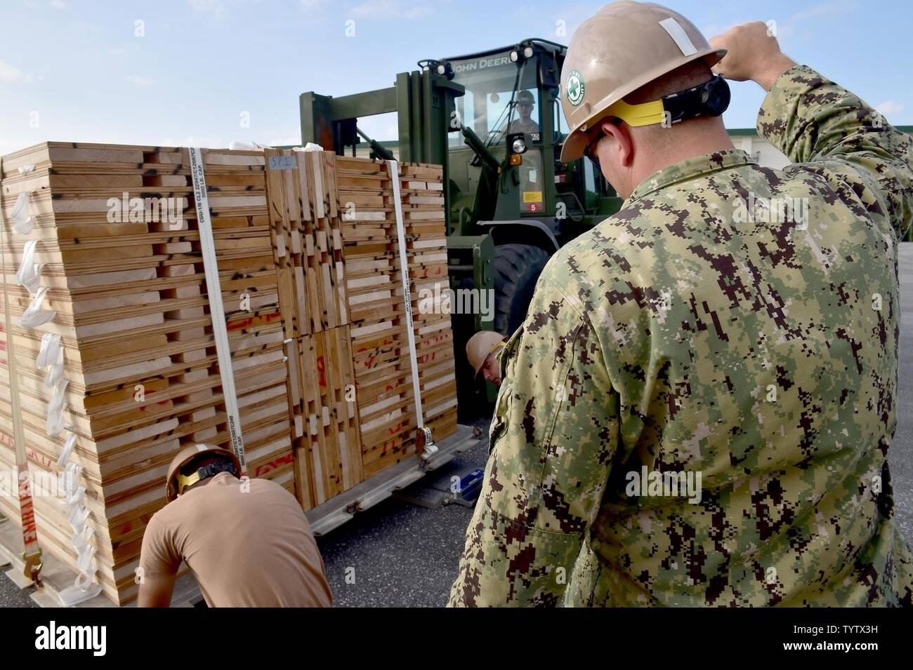 Japan (Nov 29, 2016) Petty Officer 2nd Class Bernard Barbuto, a Seabee assigned to Naval Mobile Construction Battalion (NMCB) 5, gives directions to a forklift operator while weighing a pallet on Camp Shields during an embark exercise. The exercise tests the commands ability to mobilize within 48 hours to react to different types of types of contingency operations around the world. NMCB 5 is the forward deployed Western Pacific NMCB ready to support Major Combat Operations, Humanitarian Assistance and Disaster Relief operations, and to provide general engineering and civil support to Navy, Mar Stock Photo