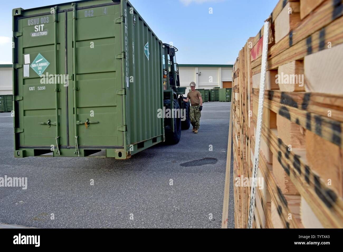 OKINAWA, Japan (Nov. 29, 2016) Petty Officer 2nd Class Nicholas Kerver, assigned to Naval Mobile Construction Battalion (NMCB) 5, gives directions to a forklift operator placing a container on line with others on Camp Shields during an embark exercise. The exercise tests the commands ability to mobilize within 48 hours to react to different types of types of contingency operations around the world. NMCB 5 is the forward deployed Western Pacific NMCB ready to support Major Combat Operations, Humanitarian Assistance and Disaster Relief operations, and to provide general engineering and civil sup - Stock Image