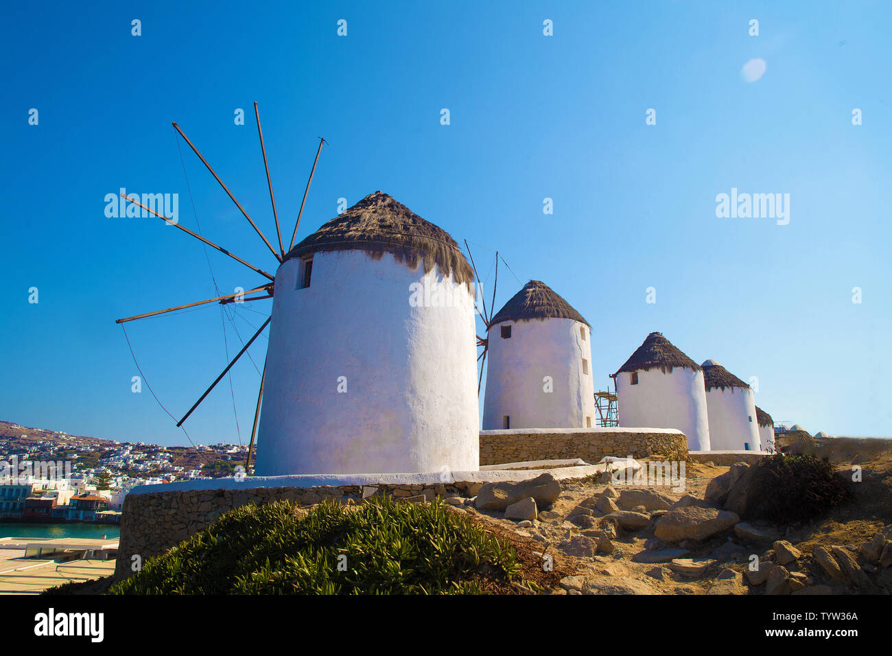 Famous mills on Mykonos    island.  and 2 persons  (at  far  distance)  making photo.  Beautiful   morning   on greek island.  Beautiful   morning   o - Stock Image