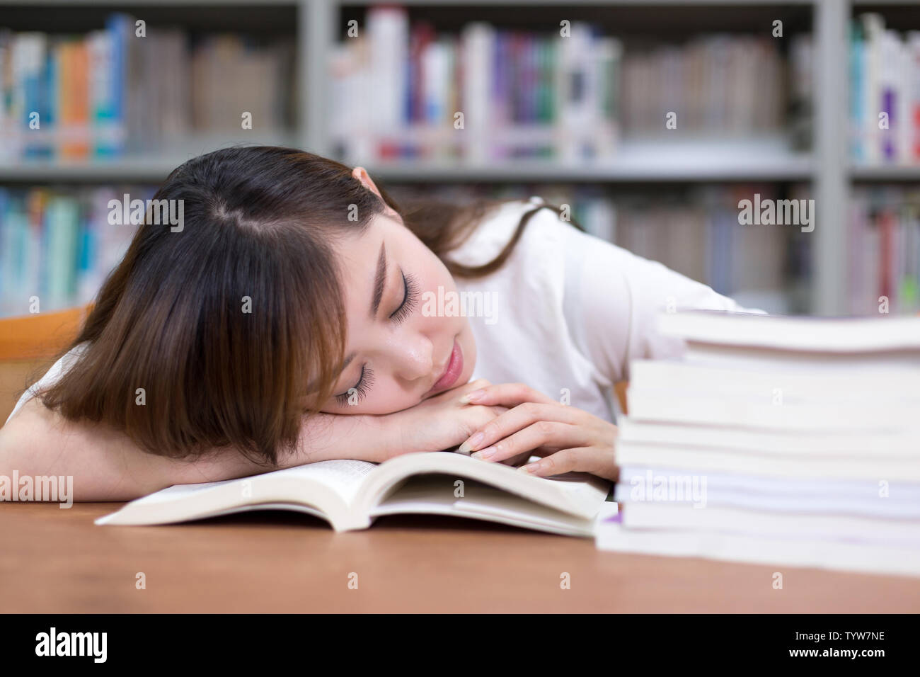 Beautiful asian femle student take nap in library during studying stack of books. - Stock Image