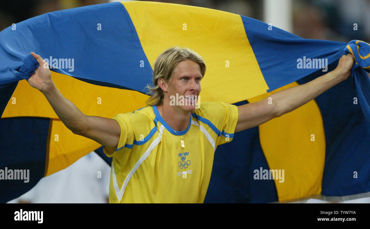 Christian Olsson of Sweden trails the flag after winning gold in ...