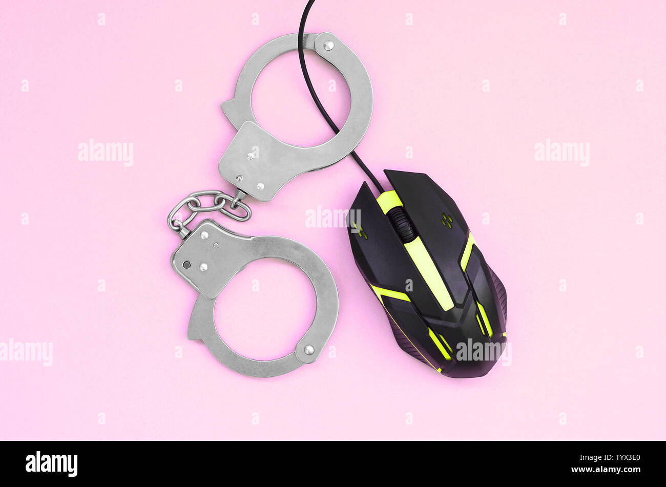 Computer mouse in a yellow color is chained in handcuffs on the background of pink color. The concept of combating computer crime, hackers and piracy. - Stock Image