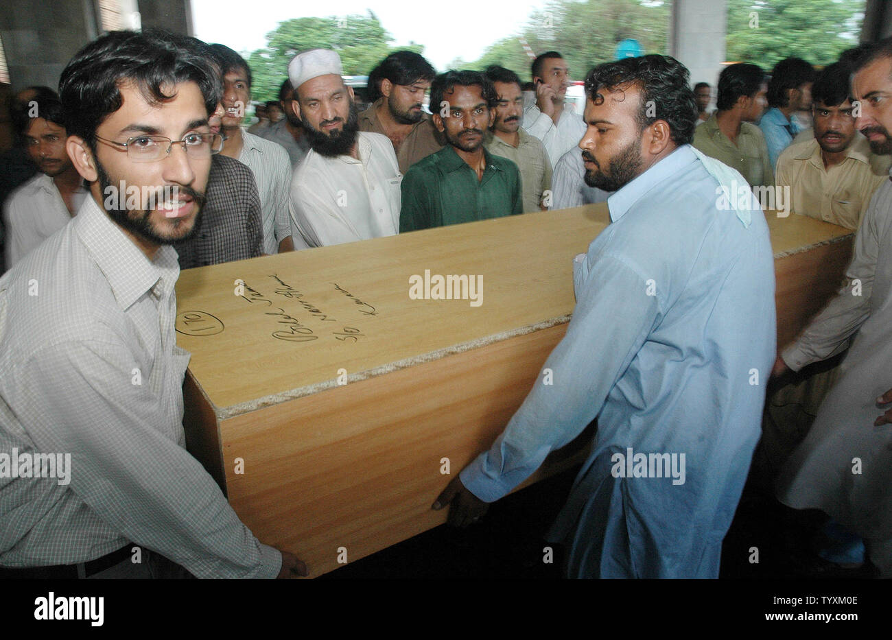 Pakistani relatives and officials lift a coffin carrying a plane crash victim's remains transported from PIMS hospital  to Islamabad airport on July 29, 2010. Pakistan observed a day of mourning for the 152 people killed in its worst aviation disaster July 28, as a monsoon deluge delayed the search for the aircraft's black box in hilly woodland.  UPI/Sajjad Ali Qureshi - Stock Image