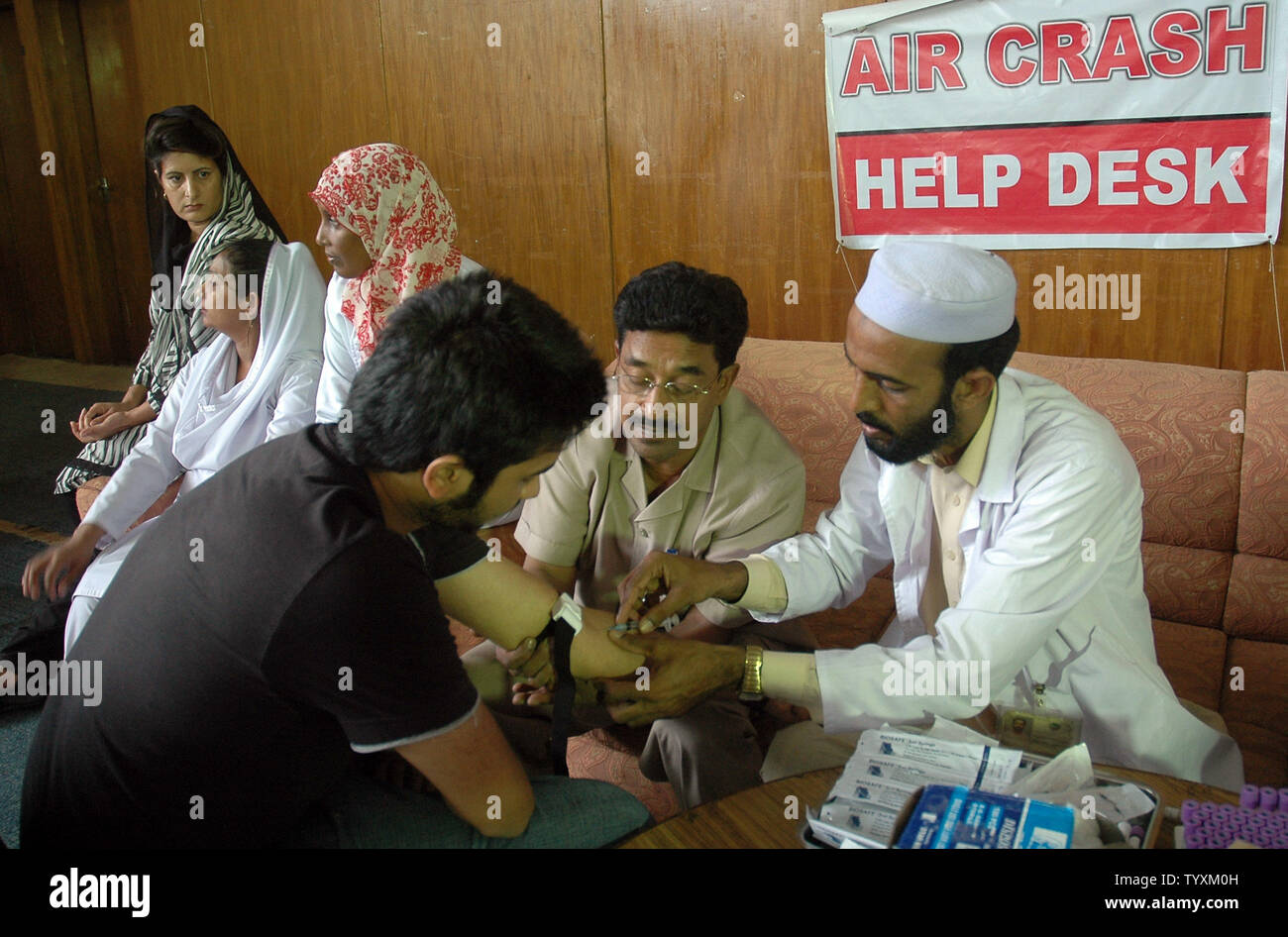 A  man gives a blood sample for his DNA to be used in identifying remains of relatives killed in a plane crash at a help center in Islamabad on July 29, 2010.  Pakistan observed a day of mourning for the 152 people killed in its worst aviation disaster July 28, as a monsoon deluge delayed the search for the aircraft's black box in hilly woodland.  UPI/Sajjad Ali Qureshi - Stock Image