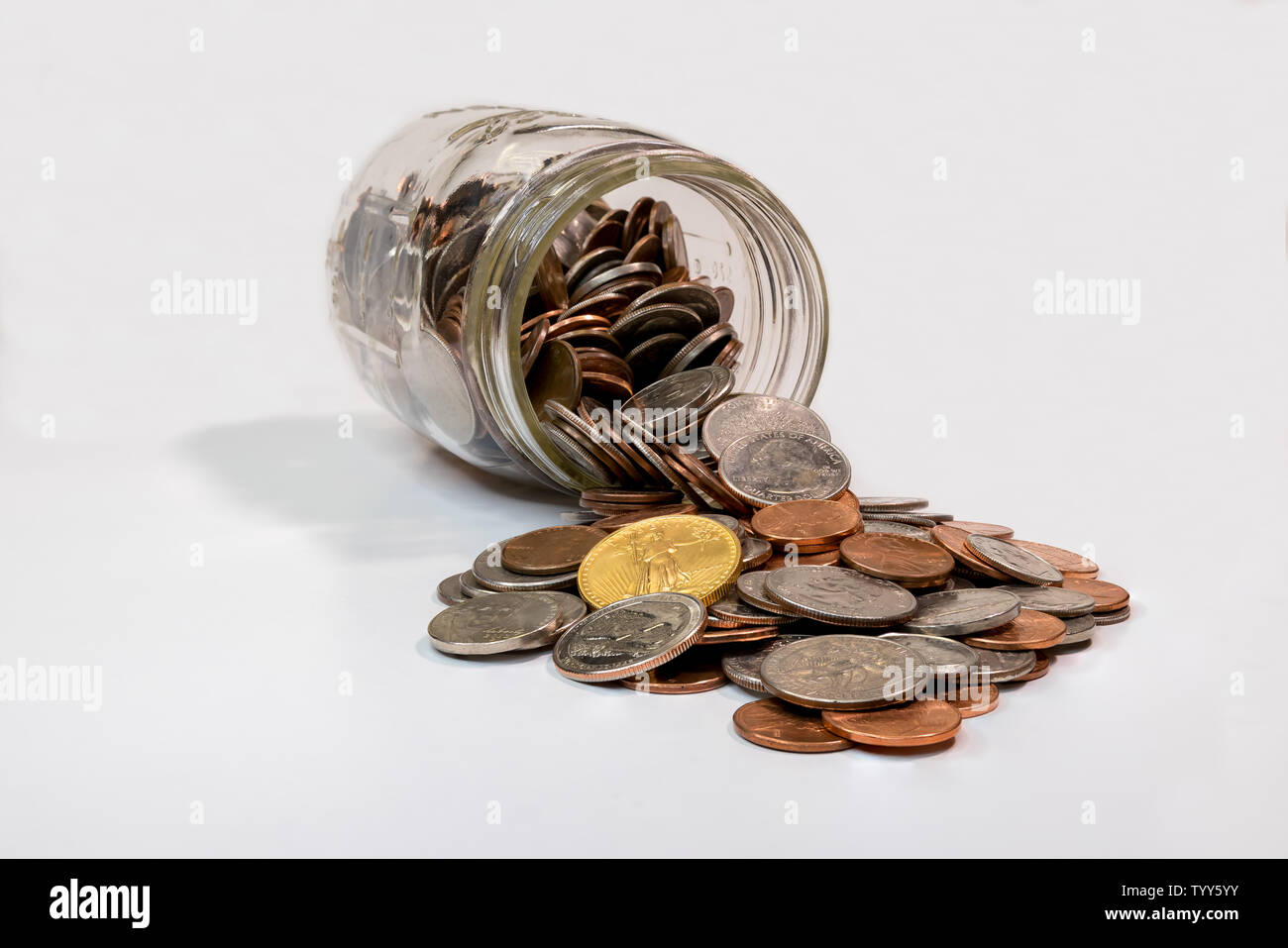 Spare change jar laying on its side with coins spilling out - Stock Image