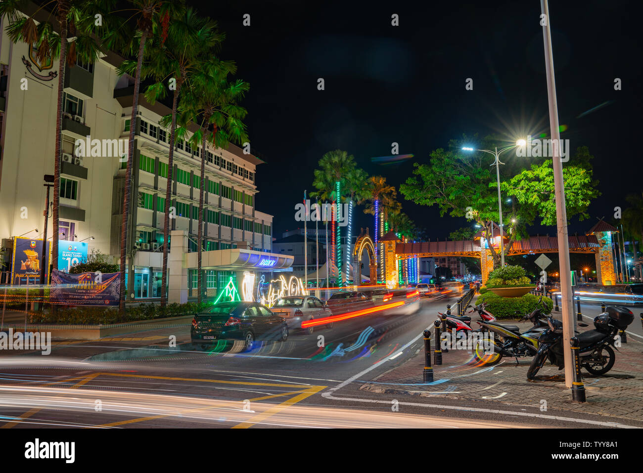 KOTA KINABALU BORNEO - MAY 30 2019; Street scene with neon lights and light trails and patterns from moving cars in long exposure - Stock Image