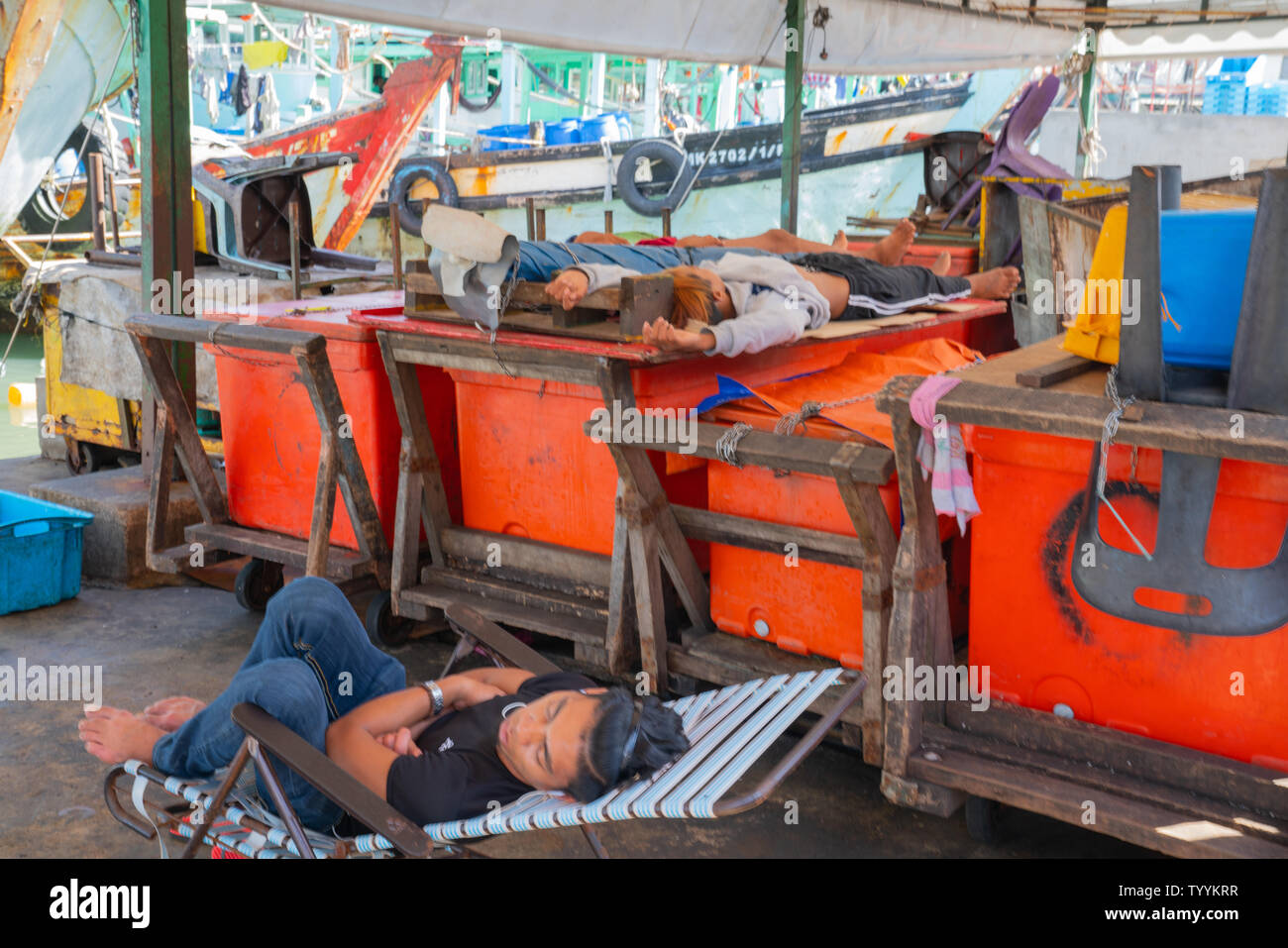 KOTA KINABALU BORNEO - MAY 31 2019; Fishermen asleep on docks near city fishing fleet moored at docks ready to head out again to catch - Stock Image