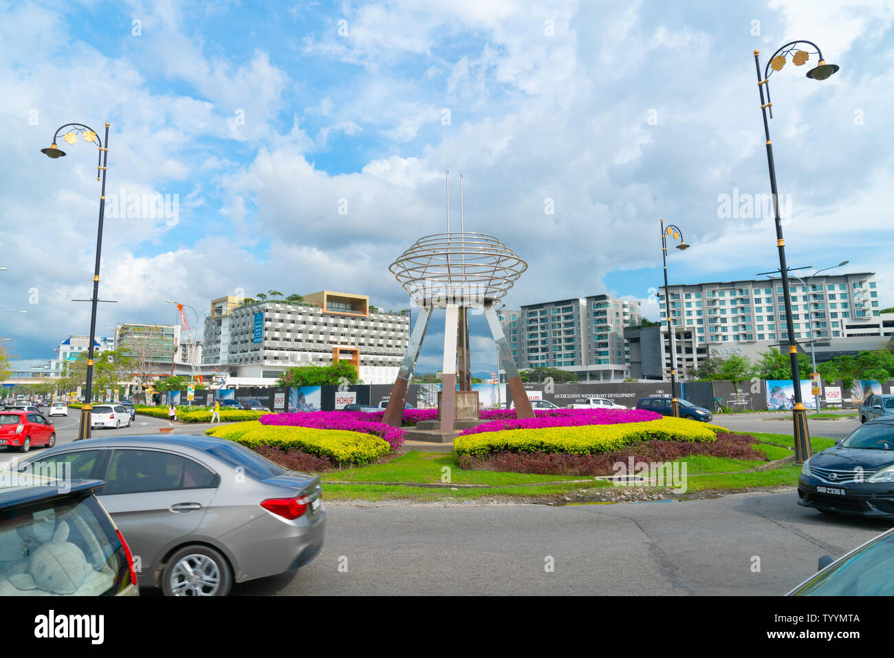 KOTA KINABALU BORNEO - JUNE 1 2019; Outstanding stainless steel public art, sculpture on vehicle roundabout in Kota Kinabalu with colorful gardens and - Stock Image