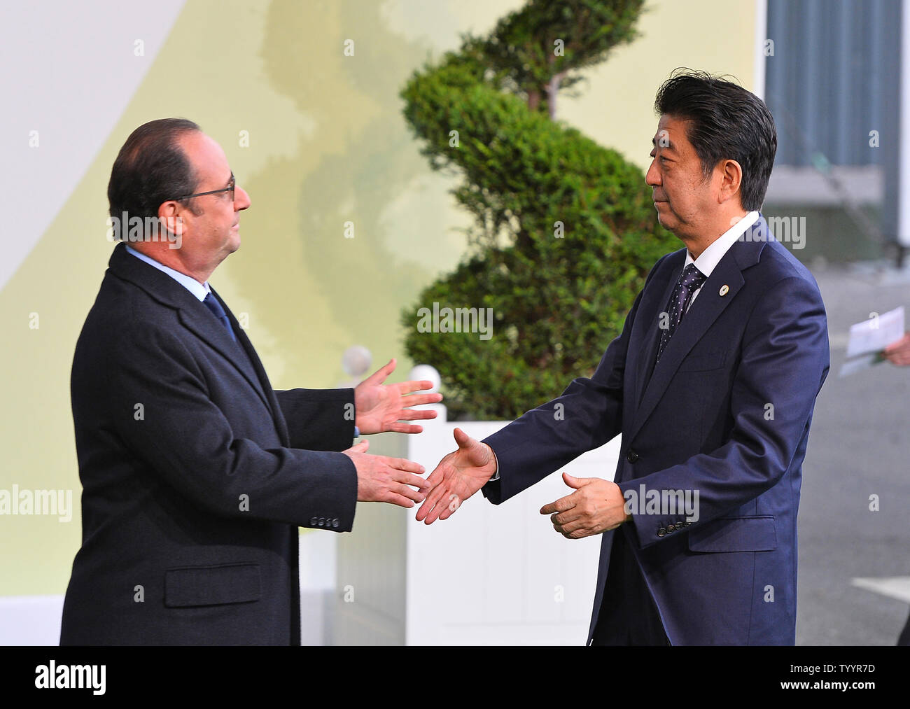 Japanese Prime Minister Shinzo Abe (R) is greeted by French President Francois Hollande at the United Nation's 21st climate change conference at Le Bourget near Paris on November 30, 2015. The almost 150 heads of state and representatives from 200 countries in attendance will attempt to negotiate a legally binding agreement to limit worldwide carbon emissions with the goal of keeping global warming under 2 degrees Celsius.   Photo by David Silpa/UPI - Stock Image