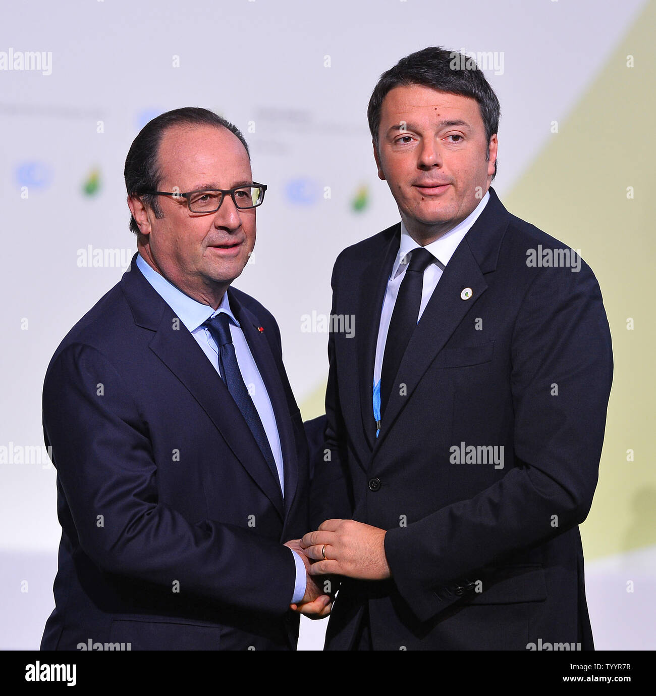 Italian Prime Minister Matteo Renzi (R) is greeted by French President Francois Hollande at the United Nation's 21st climate change conference at Le Bourget near Paris on November 30, 2015. The almost 150 heads of state and representatives from 200 countries in attendance will attempt to negotiate a legally binding agreement to limit worldwide carbon emissions with the goal of keeping global warming under 2 degrees Celsius.   Photo by David Silpa/UPI - Stock Image