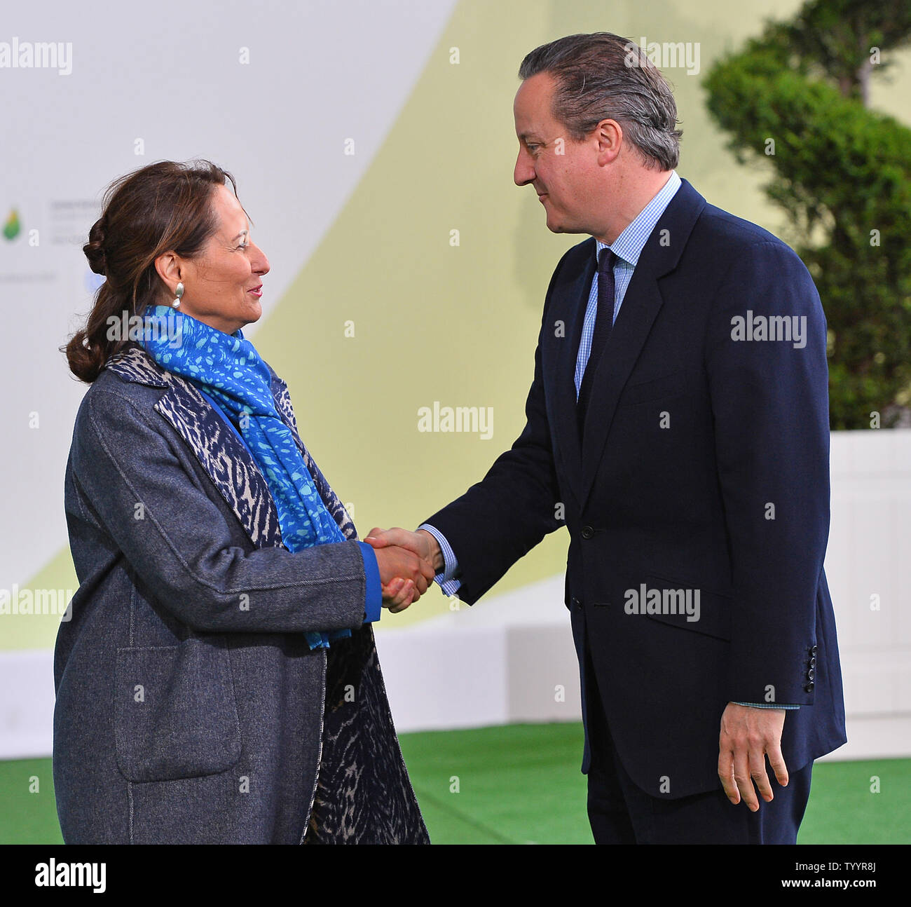 British Prime Minister David Cameron (R) is greeted by French Environment Minister Segolene Royal at the United Nation's 21st climate change conference at Le Bourget near Paris on November 30, 2015. The almost 150 heads of state and representatives from 200 countries in attendance will attempt to negotiate a legally binding agreement to limit worldwide carbon emissions with the goal of keeping global warming under 2 degrees Celsius.   Photo by David Silpa/UPI - Stock Image