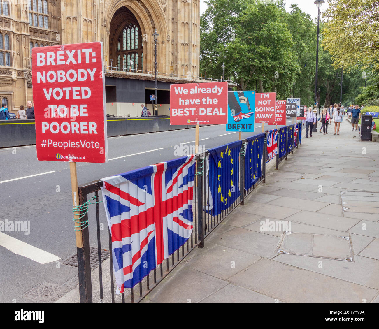 London / UK - June 26th 2019 - Pro-EU anti-Brexit signs and European Union / Union Jack flags attached to railings opposite Parliament in Westminster - Stock Image