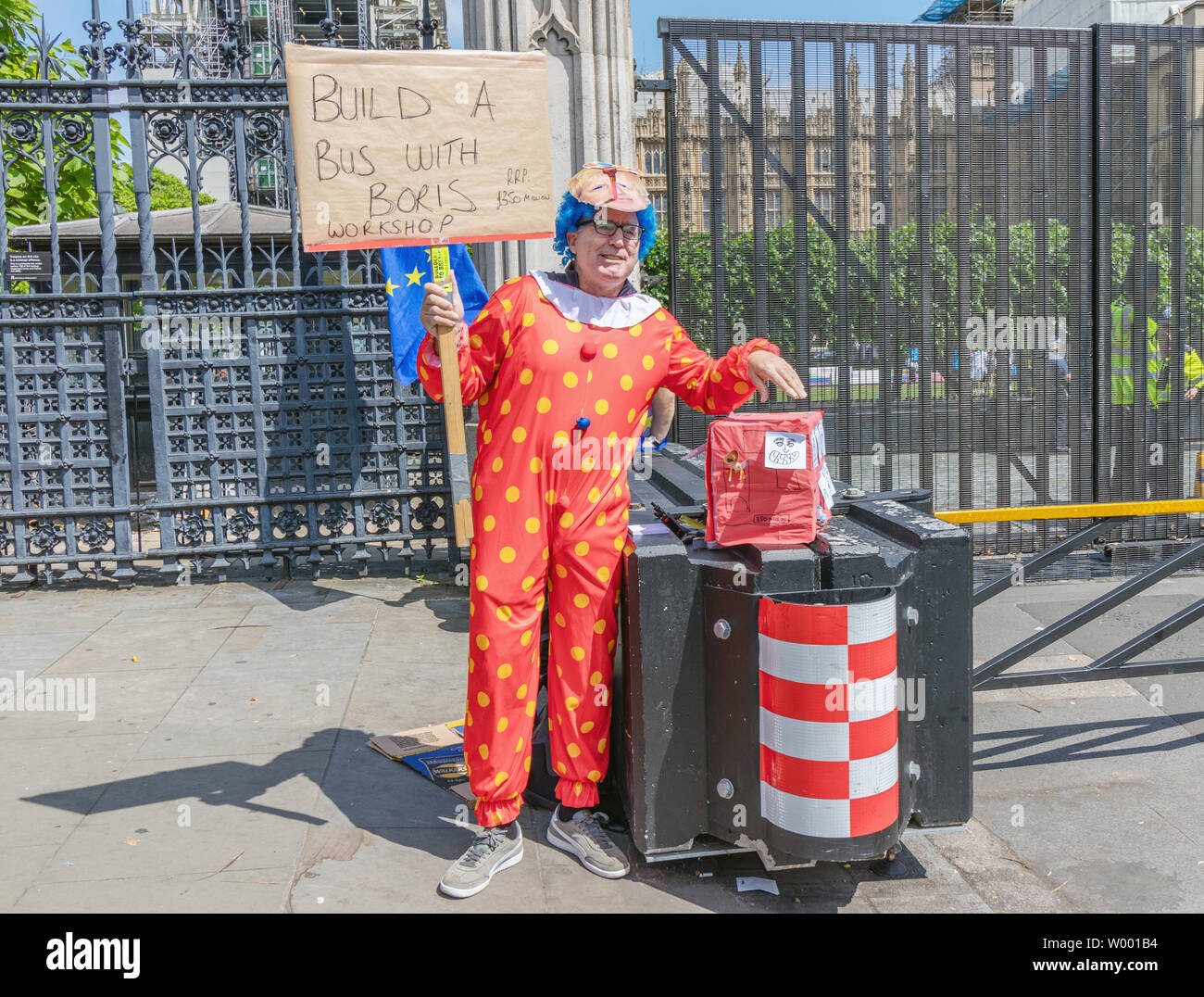 London / UK - June 26th 2019 - Pro-EU anti-Brexit protester dressed as a clown and holding a sign saying 'Build a bus with Boris workshop RRP £350mil' - Stock Image