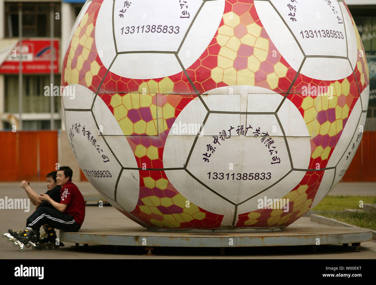 Two Chinese kids rest next to a giant inflatable soccer ball