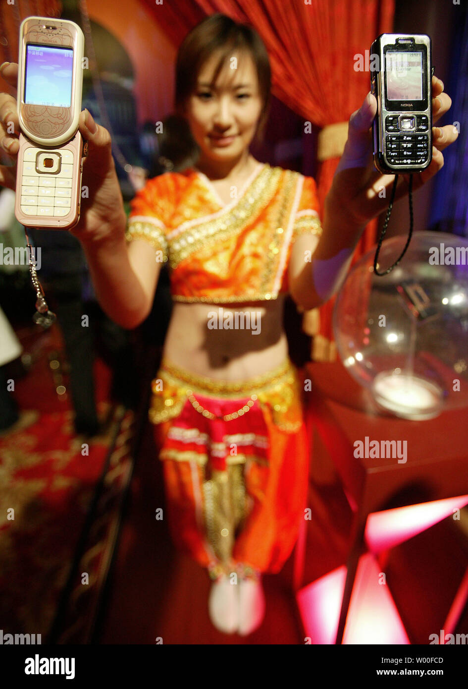 A Chinese model holds Nokia's 7373 (Left hand) and 7360 mobile phones on display at Nokia's 'Our Mobile Life 2007' conference in Beijing, China. on December 03, 2006. Nokia, the world's biggest cell- phone maker, expects the number of handset users in China to rise 11 percent to more than 500 million in 2007, boosted by growth in rural areas.  The country will add a further 160 million users from next year until 2010, Espoo, Finland-based Nokia said in a statement issued in Beijing today. China had 449 million users as of October, more than the populations of Japan and the U.S. combined.  (UPI - Stock Image