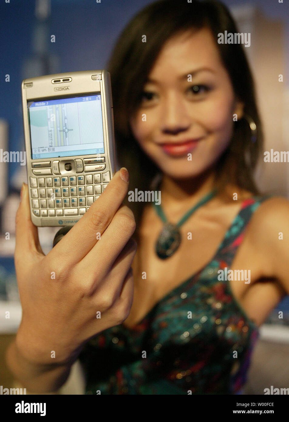 A Chinese model displays Nokia's latest mobile phone, the E62,  at Nokia's 'Our Mobile Life 2007' conference in Beijing, China. on December 03, 2006.  Nokia, the world's biggest cell- phone maker, expects the number of handset users in China to rise 11 percent to more than 500 million in 2007, boosted by growth in rural areas.  The country will add a further 160 million users from next year until 2010, Espoo, Finland-based Nokia said in a statement issued in Beijing today. China had 449 million users as of October, more than the populations of Japan and the U.S. combined.  (UPI Photo/Stephen S - Stock Image
