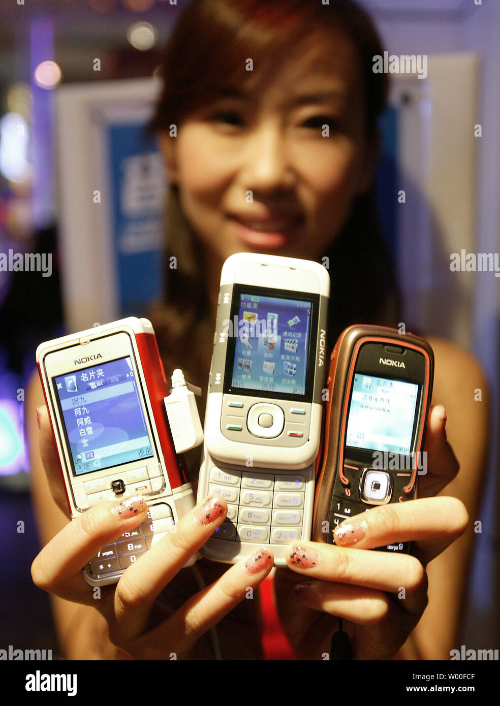 A Chinese model holds Nokia's 5000 series mobile phones on display at Nokia's 'Our Mobile Life 2007' conference in Beijing, China. on December 03, 2006. Nokia, the world's biggest cell- phone maker, expects the number of handset users in China to rise 11 percent to more than 500 million in 2007, boosted by growth in rural areas.  The country will add a further 160 million users from next year until 2010, Espoo, Finland-based Nokia said in a statement issued in Beijing today. China had 449 million users as of October, more than the populations of Japan and the U.S. combined.  (UPI Photo/Stephen - Stock Image