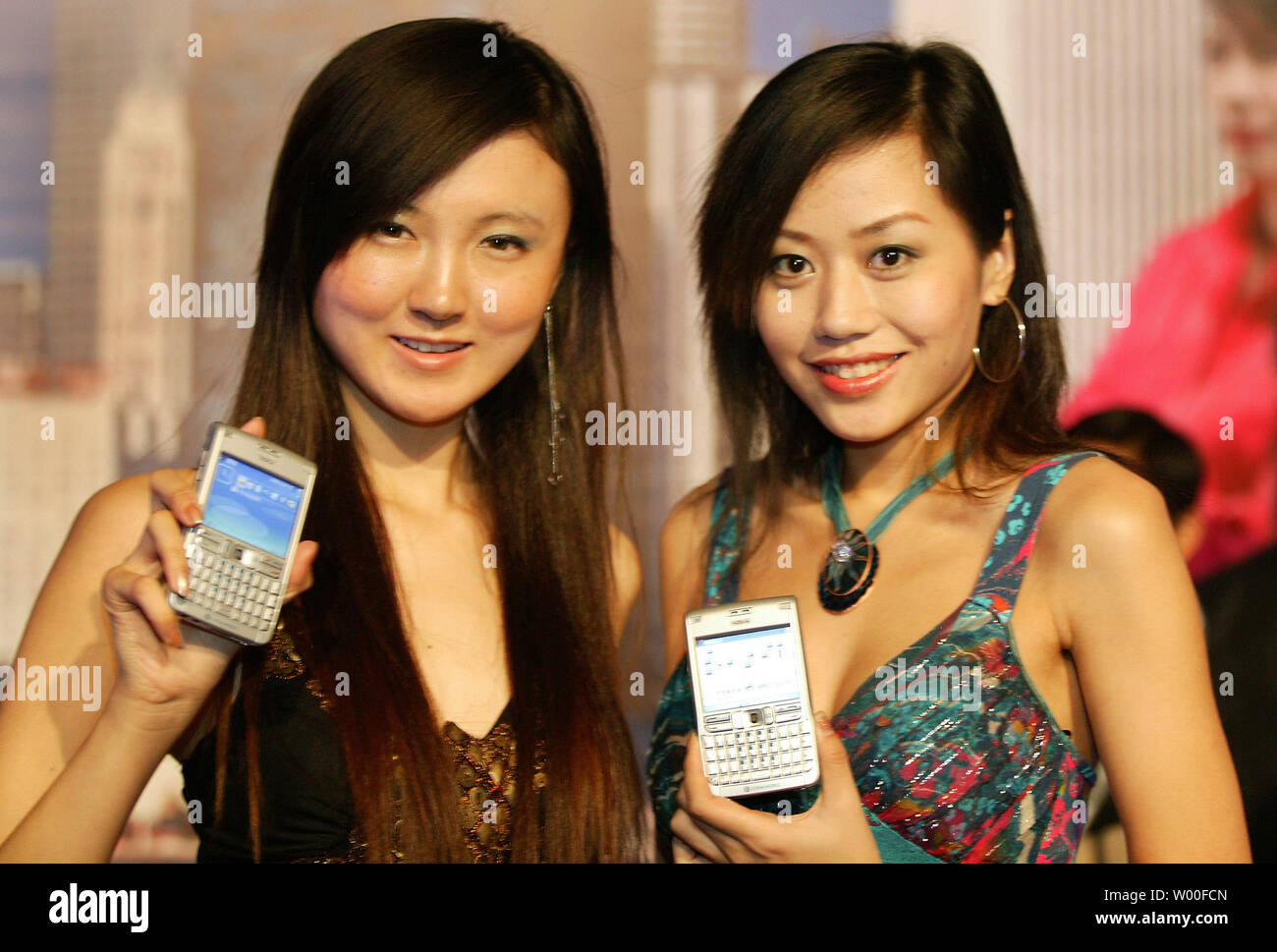 Chinese models display Nokia's latest mobile phone, the E62,  at Nokia's 'Our Mobile Life 2007' conference in Beijing, China. on December 03, 2006.  Nokia, the world's biggest cell- phone maker, expects the number of handset users in China to rise 11 percent to more than 500 million in 2007, boosted by growth in rural areas.  The country will add a further 160 million users from next year until 2010, Espoo, Finland-based Nokia said in a statement issued in Beijing today. China had 449 million users as of October, more than the populations of Japan and the U.S. combined.  (UPI Photo/Stephen Sha - Stock Image