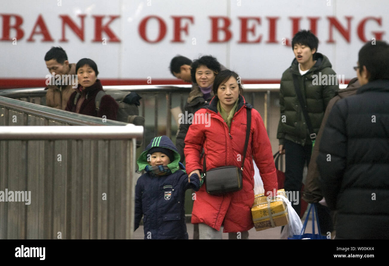Chinese walk past a Bank of Beijing in downtown Beijing February 8, 2009.  The Year of the Bull may be underway in China, but the Chinese economic outlook is the most bearish in years. Few economists argue that China remains the engine of future world economic growth, but it suffered along with other emerging markets last year as the brakes were slammed on the global economy.  (UPI Photo/Stephen Shaver) - Stock Image
