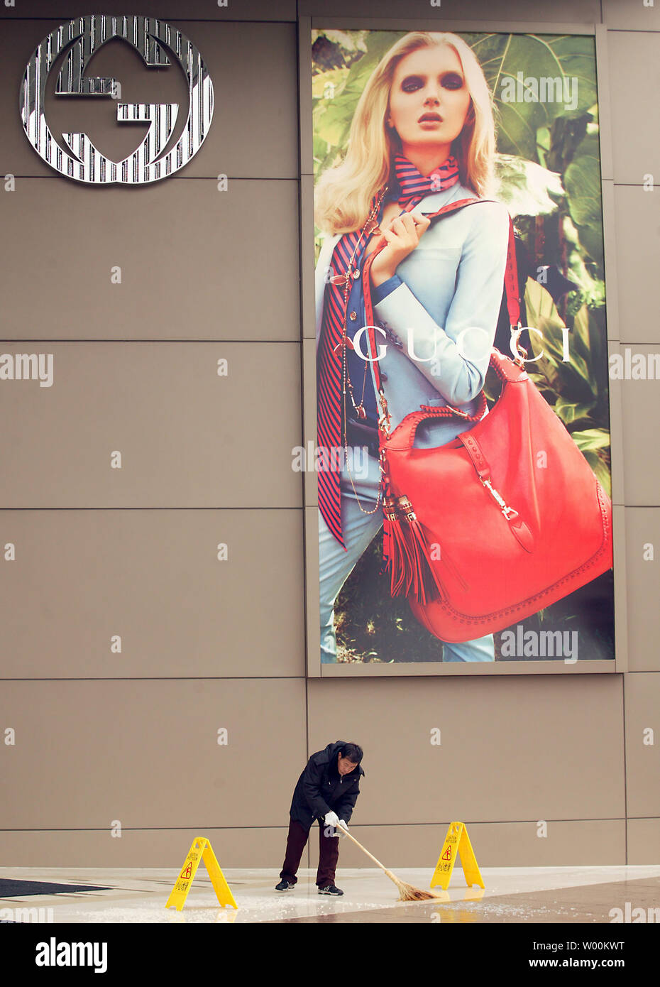 A Chinese worker is dwarfed by a massive Dolce Gabbana showroom boutique in central Beijing February 19, 2009.  In the last decade, most European designers have shifted production to China, including brands like Dolce & Gabbana, Prada, and Armani.   (UPI Photo/Stephen Shaver) - Stock Image