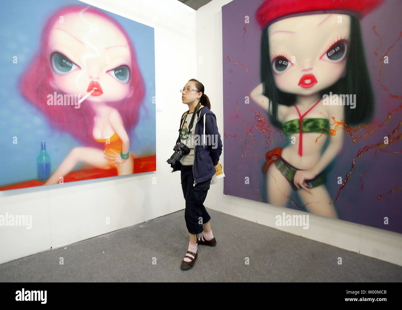 682268d32 A Chinese woman looks at some paintings by famous Chinese contemporary  artist Wang Zhijie being exhibited