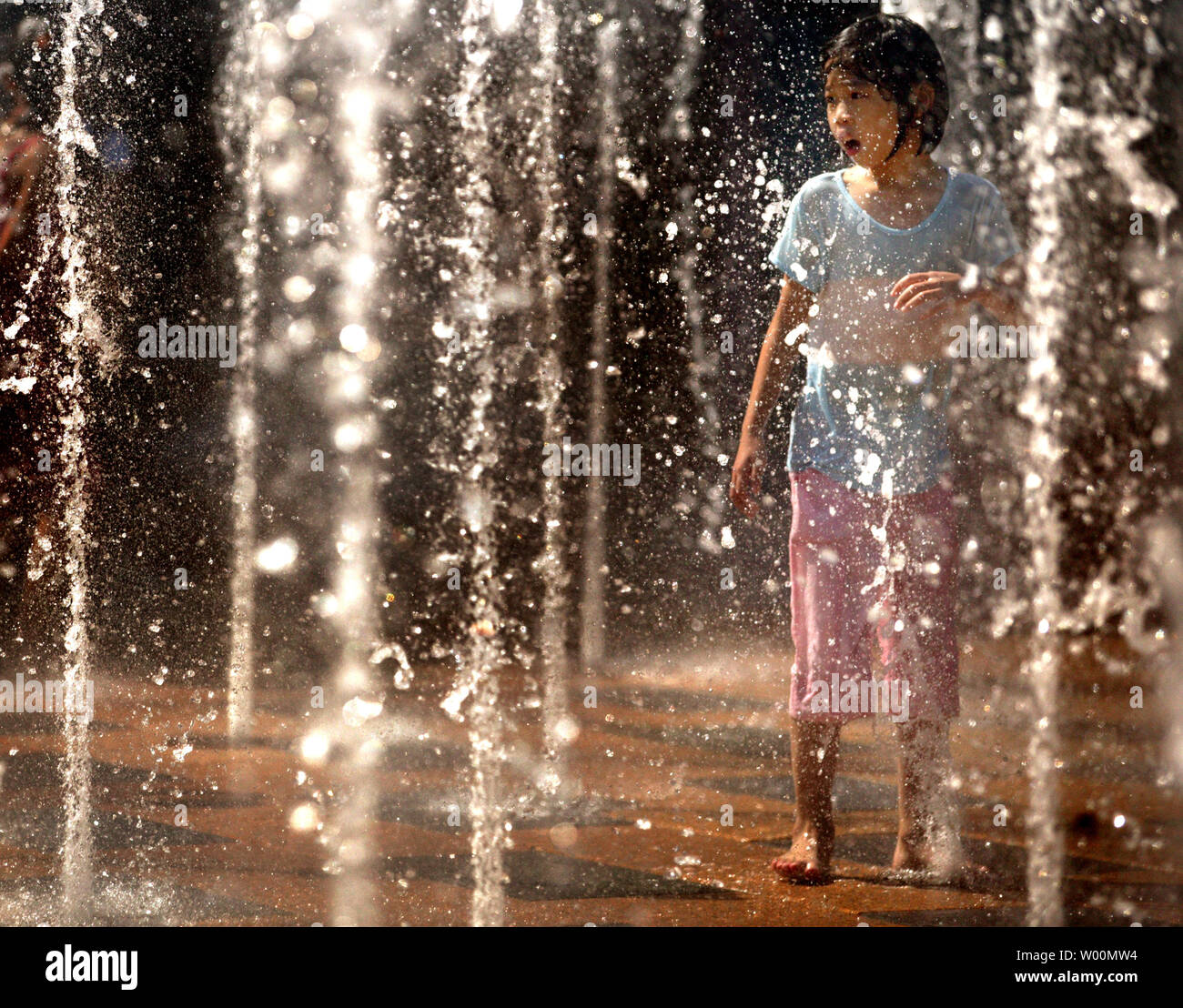 A Chinese girl plays in a public water fountain just outside