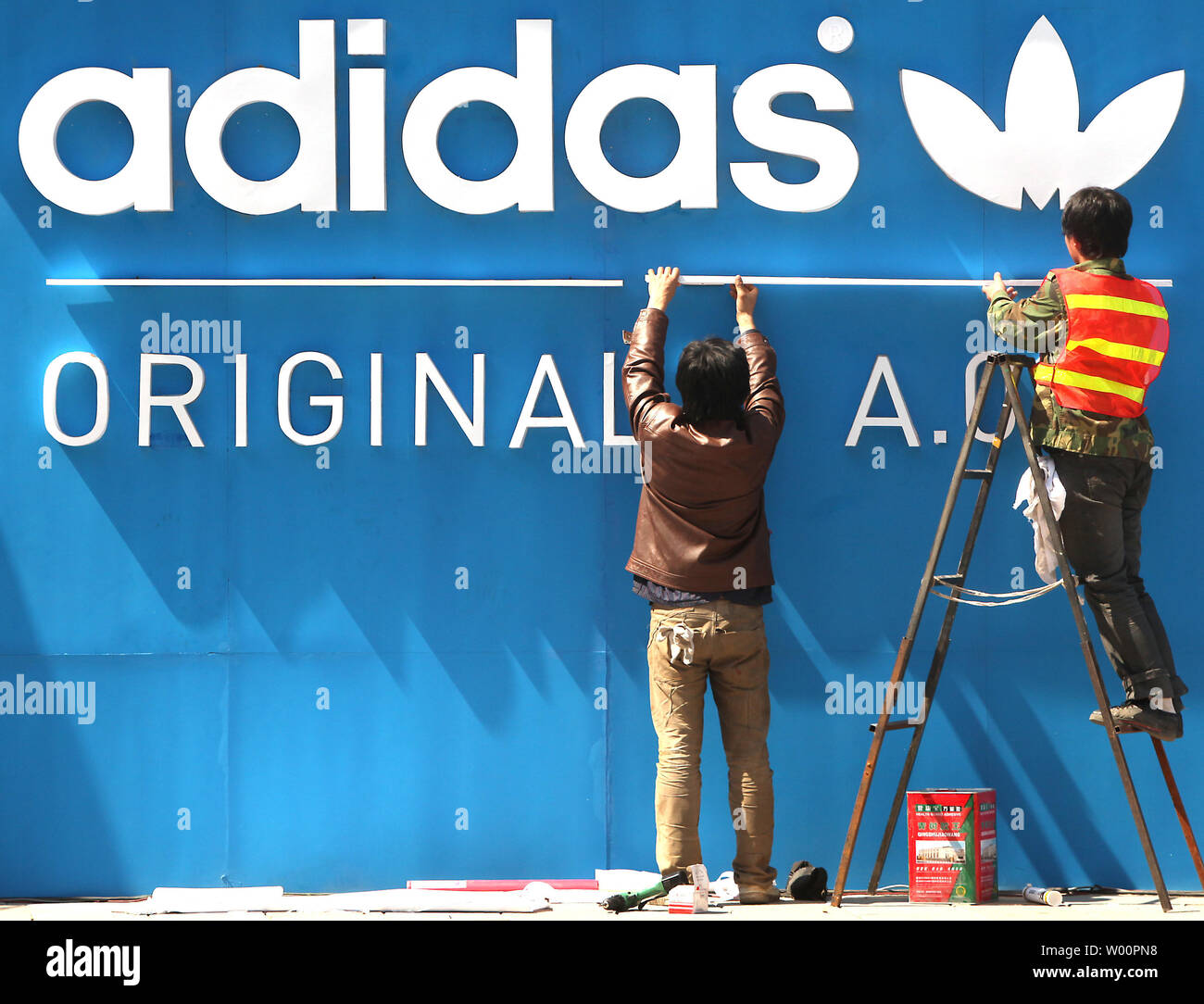 Distribuir Me preparé cocinar una comida  Chinese workers put up an Adidas advertisement on the front of a new,  international fashion mall in Beijing on April 6, 2010. Many economists say  that the world's fastest growing economy, China,