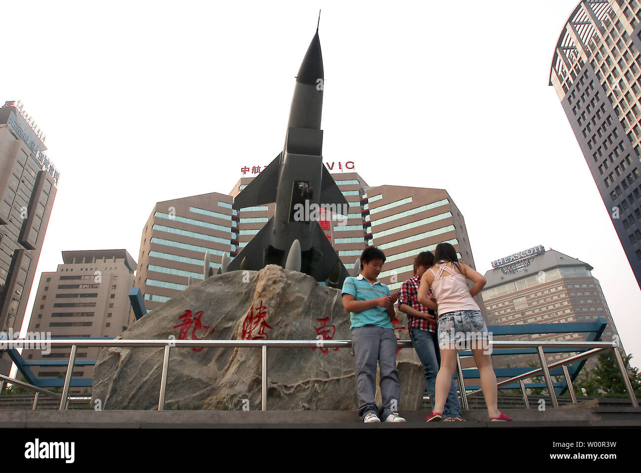 Chinese teenagers hang out under a Chinese fighter jet on display in front of a main military aviation ministry complex in downtown Beijing on June 06, 2010.  The United States appealed to China on Saturday to restore military ties despite discord over U.S. arms sales to Taiwan and said it was considering options beyond the United Nations to punish North Korea over the sinking of a South Korean naval ship.     UPI/Stephen Shaver - Stock Image