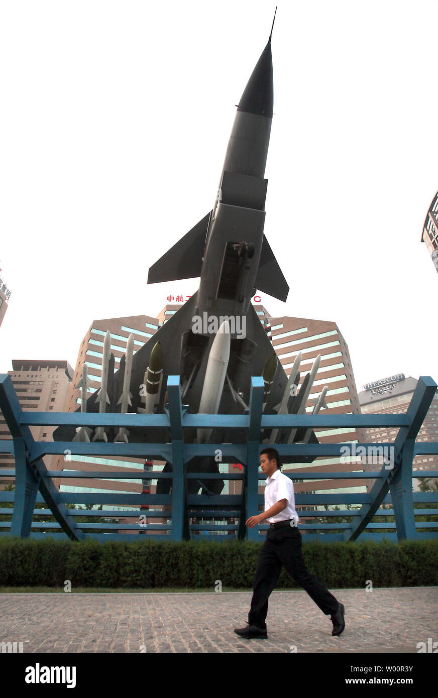 Chinese walk past a Chinese fighter jet on display in front of a main military aviation ministry complex in downtown Beijing on June 06, 2010.  The United States appealed to China on Saturday to restore military ties despite discord over U.S. arms sales to Taiwan and said it was considering options beyond the United Nations to punish North Korea over the sinking of a South Korean naval ship.     UPI/Stephen Shaver - Stock Image