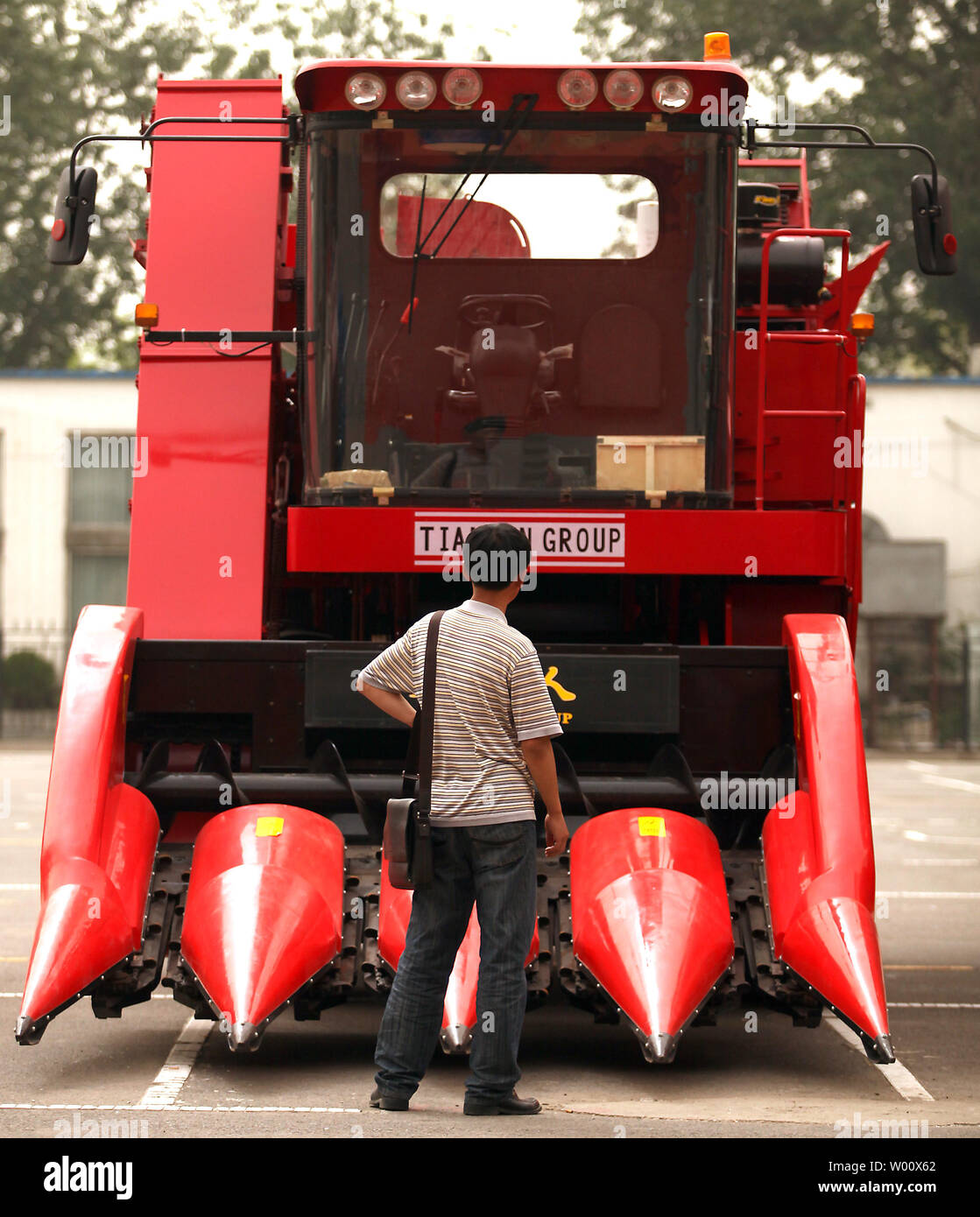 A Chinese man looks at a made-in-China combine harvester on