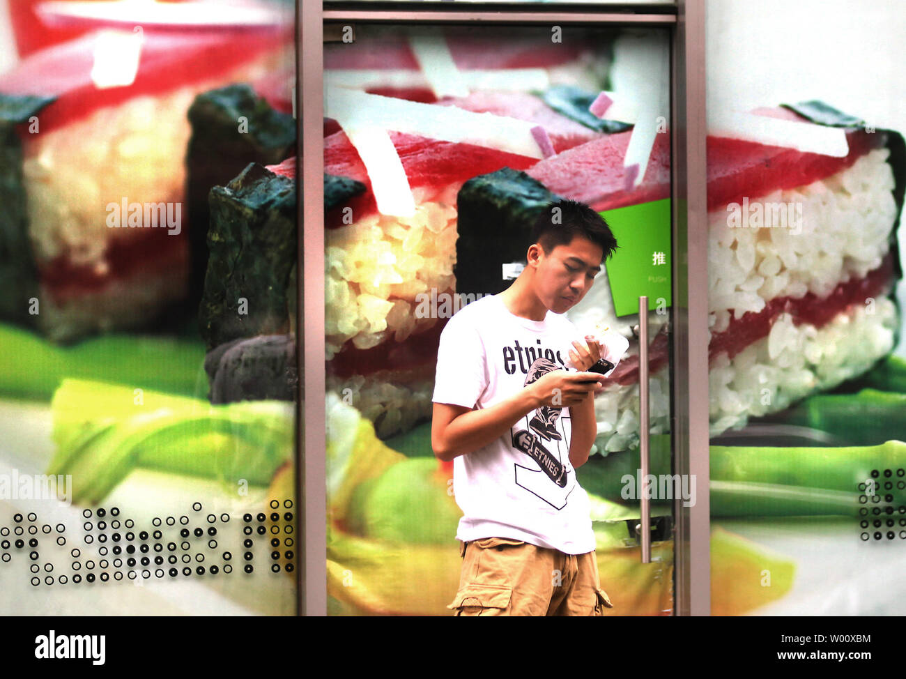 A Chinese man eats a sandwich while texting outside a