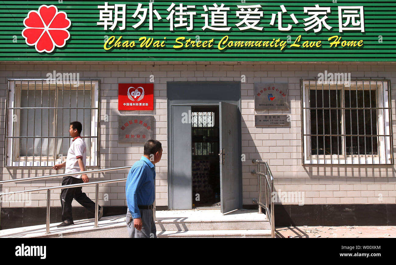 Chinese walk by a 'Community Love Home,' a new, social welfare center built to aid the capital's greying population in Beijing July 15, 2011.  China is facing a potential time bomb over its growing elderly population, according to Chinese scholars.  Demographers have warned that in 15 or 20 years' time, china will face an ageing population similar to that encountered by several developed countries, but without the welfare resources to meet the challenge.    UPI/Stephen Shaver - Stock Image