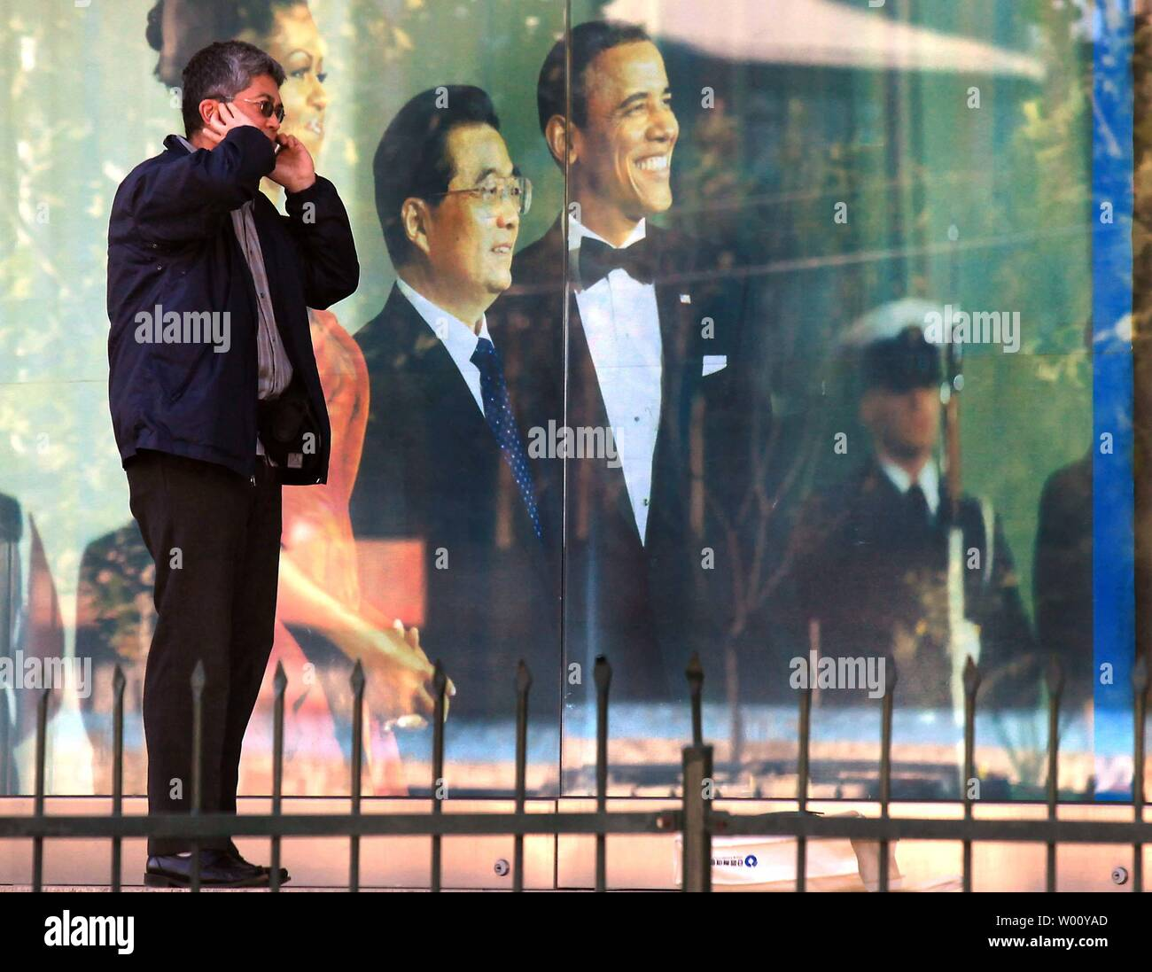 A Chinese man talks on a phone in front of the U.S. embassy's visa section, adorned with a photo of Chinese President Hu Jintao's state visit to Washington, in Beijing October 24, 2011.   The U.S. processed over 1 million visas this year in China, allowing a record number of Chinese to travel to the United States.    UPI/Stephen Shaver Stock Photo