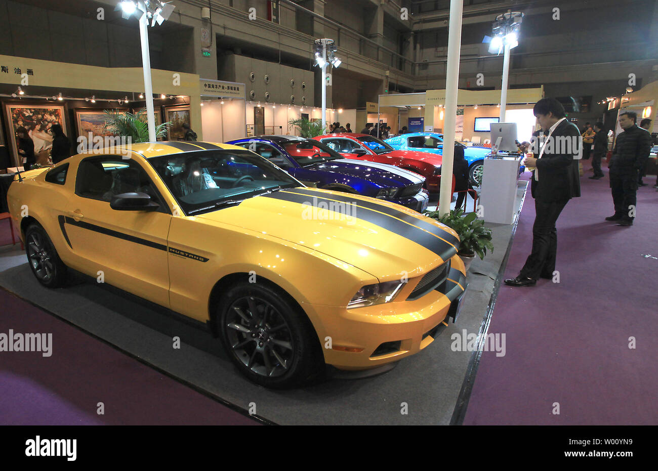 Chinese businessmen look at Shelby Mustangs on display at