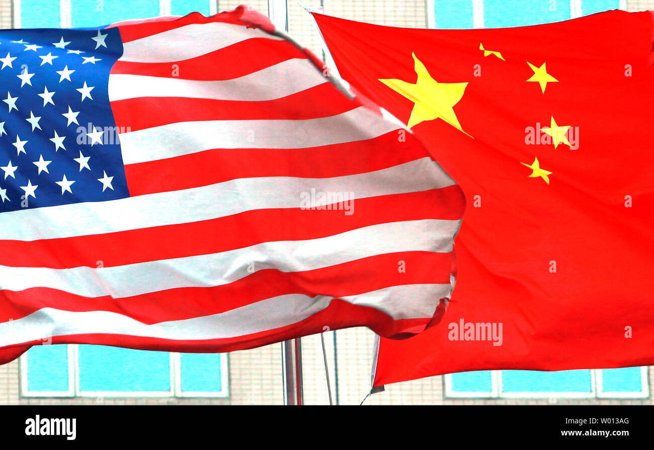 """Both American and Chinese national flags fly next to each other outside an international hotel in Beijing on July 7, 2013.  Even after months of tensions over alleged cyberattacks and continual trade disputes, the leaders of China and the United States have struck positive tones recently as both agreed on forging a """"new model"""" for their relations going forward.        UPI/Stephen Shaver Stock Photo"""