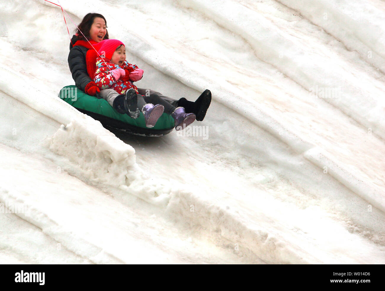 Chinese enjoy a fast downhill slide on a rubber tire at a snow park with rides built out of ice and snow in Beijing on February 15, 2014.  China's capital is experiencing an unusually warm winter, as with many cities around the world that are also experiencing unusually warm or cold weather.    UPI/Stephen Shaver - Stock Image