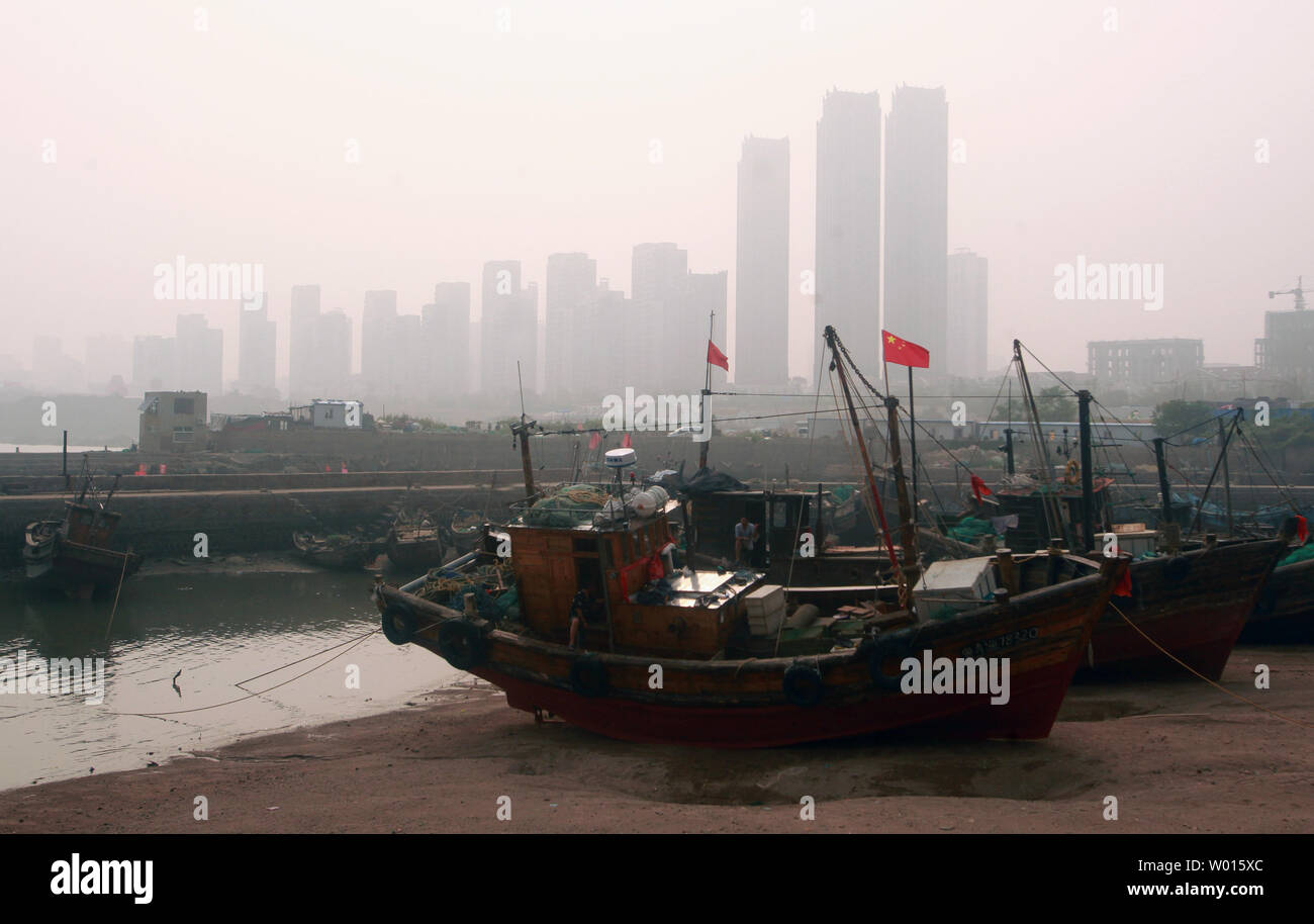 Chinese fishing boats wait for the coming high tide from the Yellow Sea in an old, small harbor in the coastal city Qingdao, a major city in eastern Shandong Province, on August 17, 2014.  Qingdao is a major seaport, naval base and industrial center.  The world's longest sea bridge, the Jiaozhou Bay Bridge, links the main urban area to Huangdao.      UPI/Stephen Shaver - Stock Image