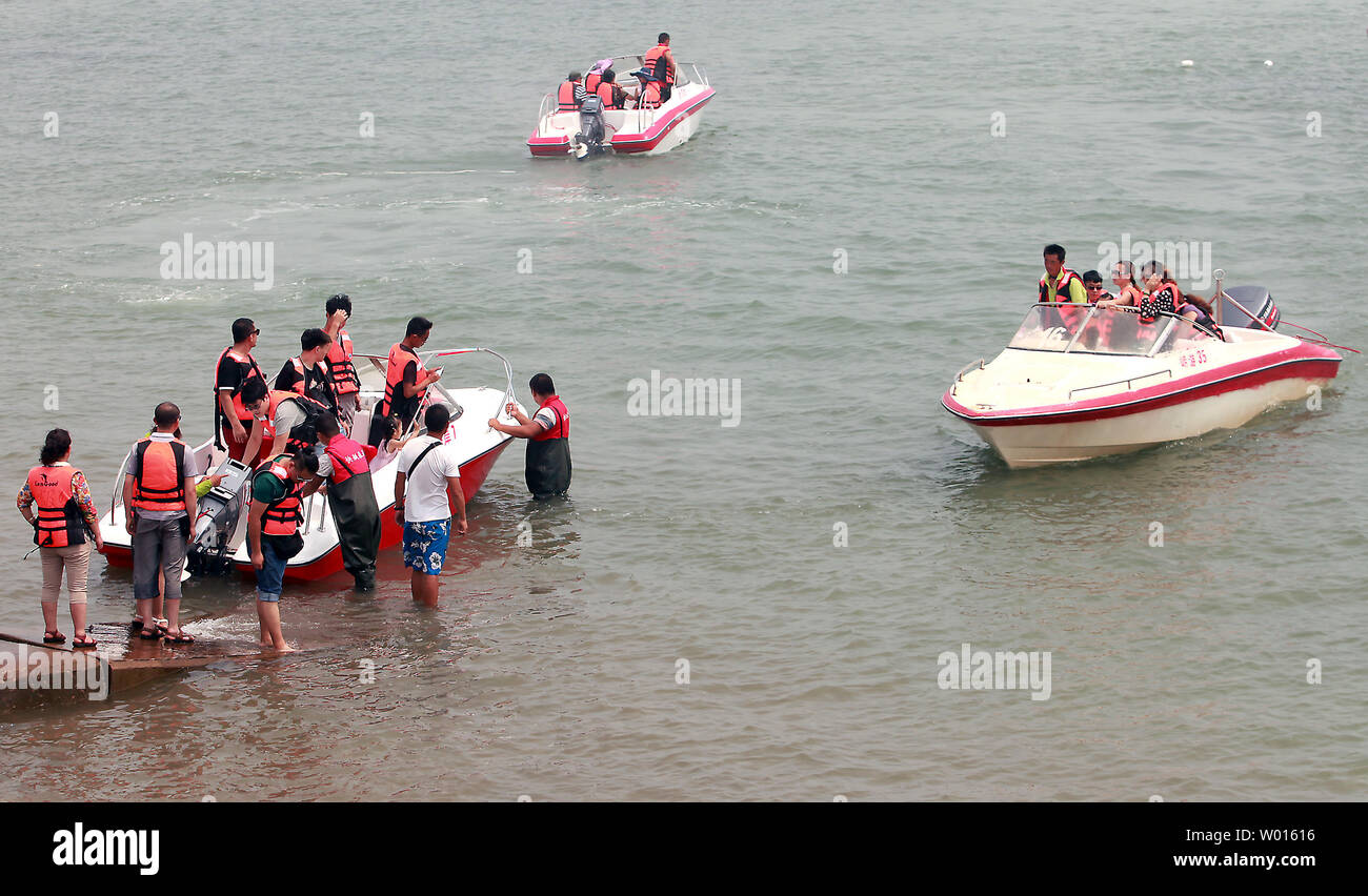 Chinese tourists pay to ride speed boats near the shore of the coastal city Qingdao, a major port in eastern Shandong Province, on August 19, 2014.  China aims to double domestic spending on tourism by 2020 by offering financial support to develop the growing sector, according to the government, as it seeks to boost spending at home to spur economic growth.    UPI/Stephen Shaver Stock Photo