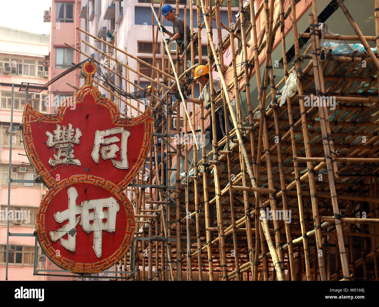 Workers assemble bamboo scaffolding around a housing estate in Hong Kong on October 13, 2014.  Hong Kong offices and homes are the world's least affordable, costing almost 15 times household incomes in 2013, according to the Demographia International Housing Affordability survey.      UPI/Stephen Shaver - Stock Image