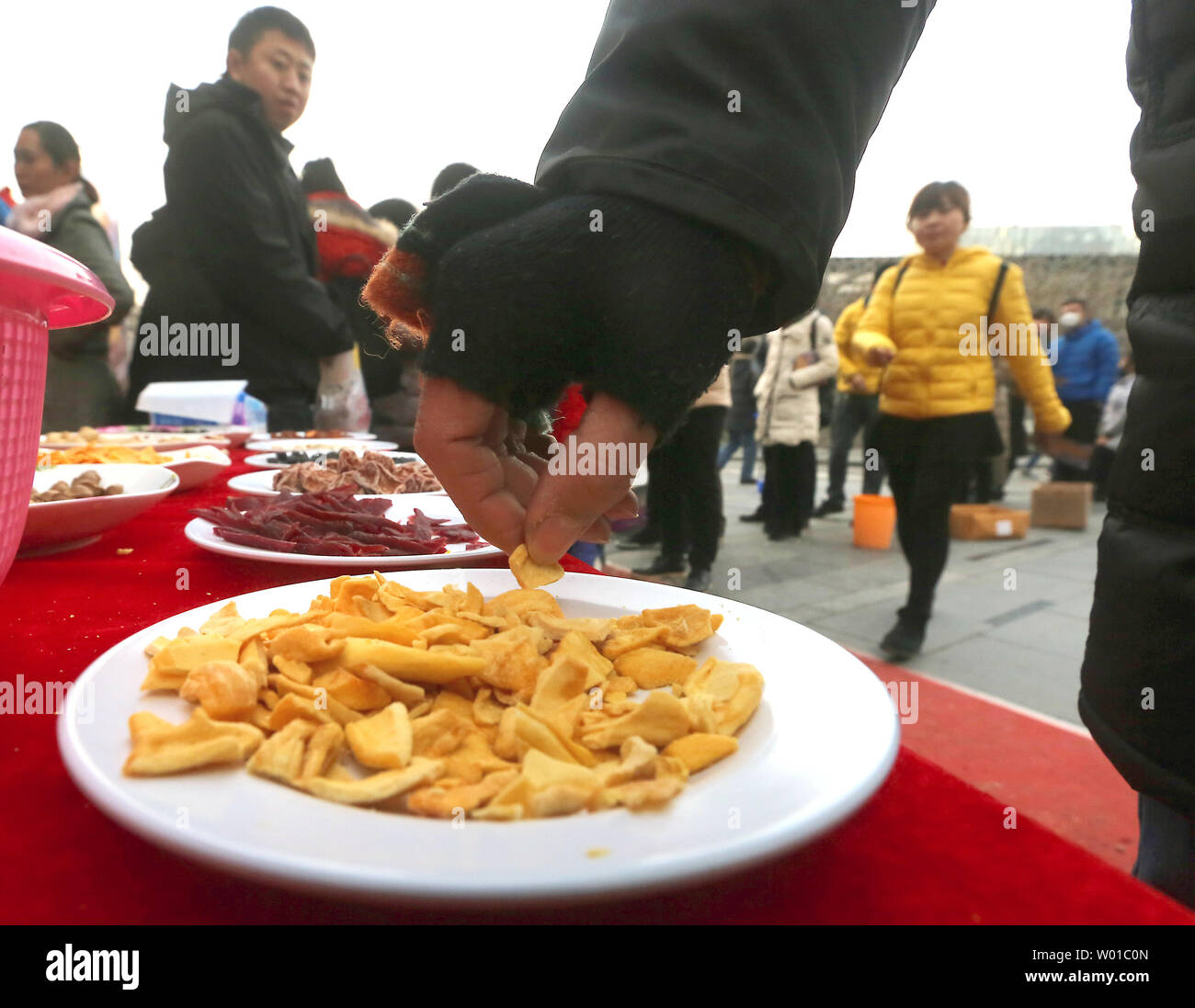 Chinese try samples of free snacks outside a food store as