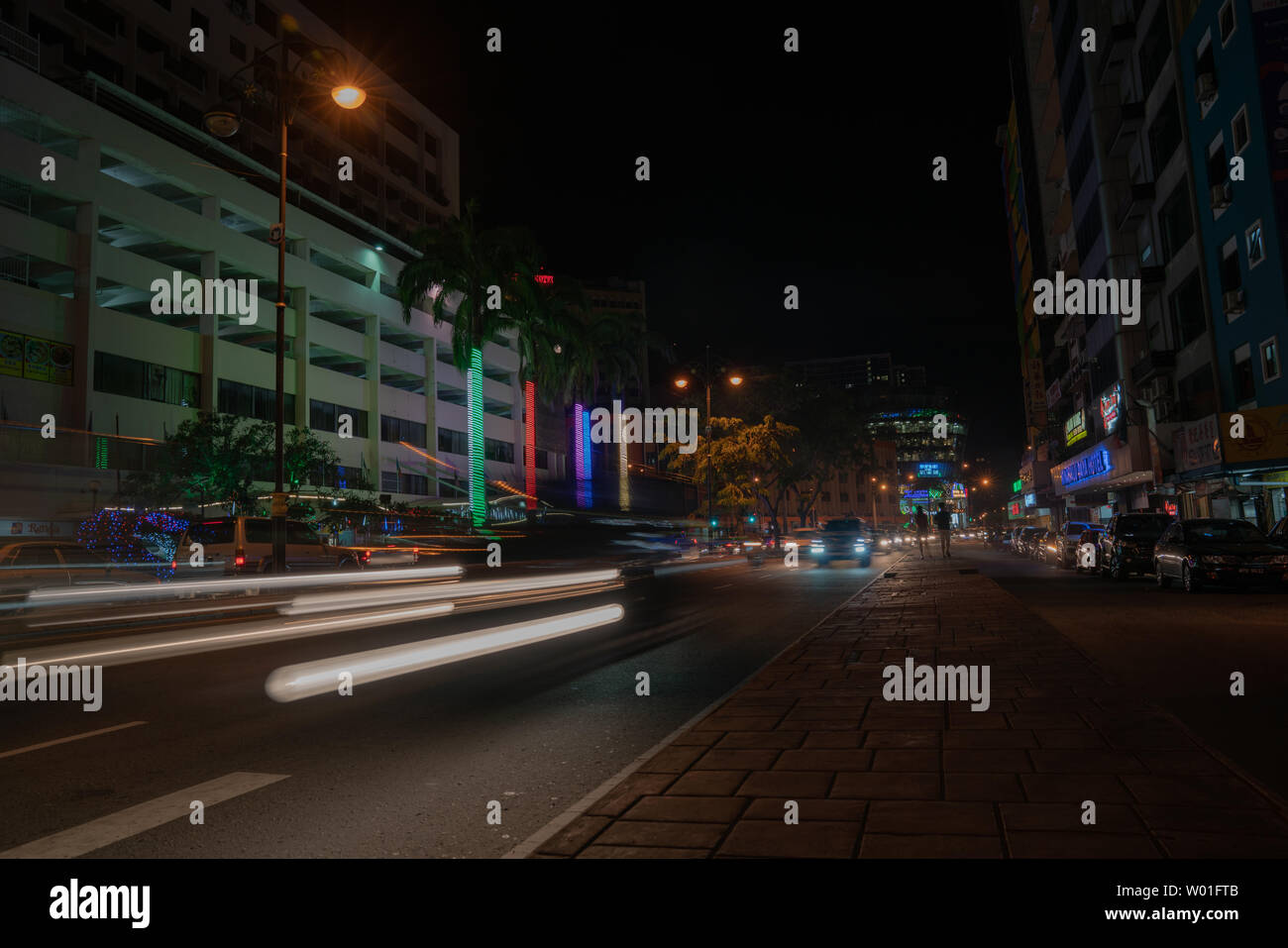 KOTA KINABALU BORNEO - MAY 30 2019; Street scene with neon lights and light trails from moving cars in long exposure - Stock Image