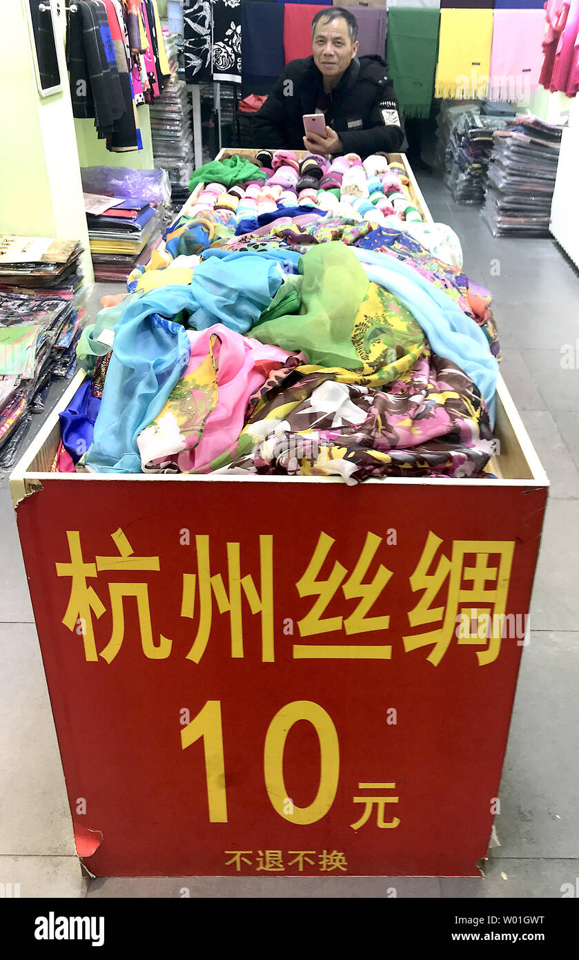 A Chinese security guard watches over clothing being sold at