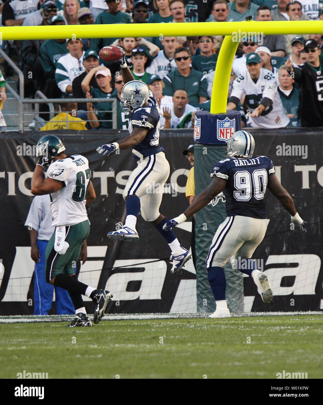 Dallas linebacker DeMarcus Ware goes high in the end zone to score for the Cowboys after recovering a Philadelphia fumble and running it for 69-yards and a touchdown during second quarter Dallas Cowboys-Philadelphia Eagles NFL football action  at Philadelphia's Lincoln Field October 8, 2006. Covering him is Dallas Jay Ratliff (#90) and giving up the chase is Eagles L.J.Smith (#82).         (UPI Photo/John Anderson) - Stock Image