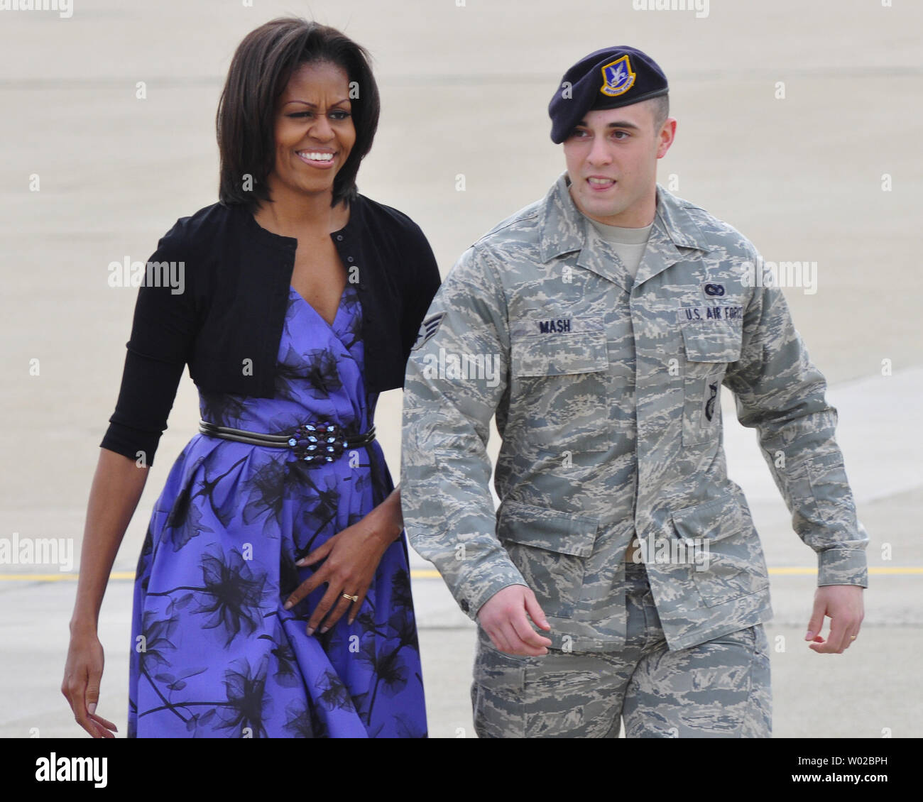 First Lady Michelle Obama walks with Senior Airman Domenic Mash (R) on the tarmac at the base for the 911th Airlift Wing of the Air Force Reserve Command and the 171st Air Refueling Wing near Pittsburgh on April 17, 2012.    UPI/Archie Carpenter Stock Photo