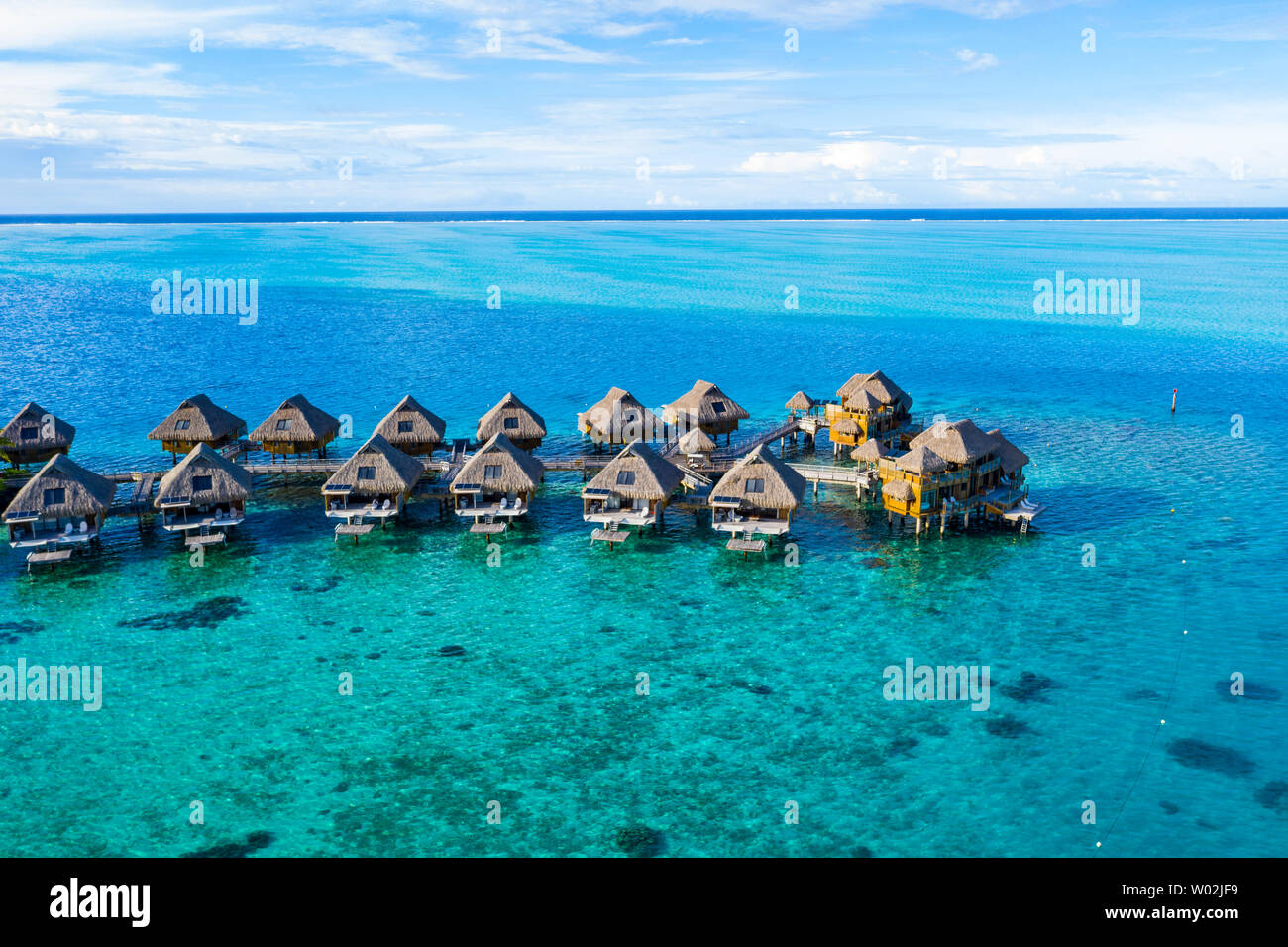 Travel vacation paradise aerial drone video with overwater bungalows in coral reef lagoon sea. Aerial video from Bora Bora, French Polynesia, Tahiti, South Pacific Ocean. Stock Photo