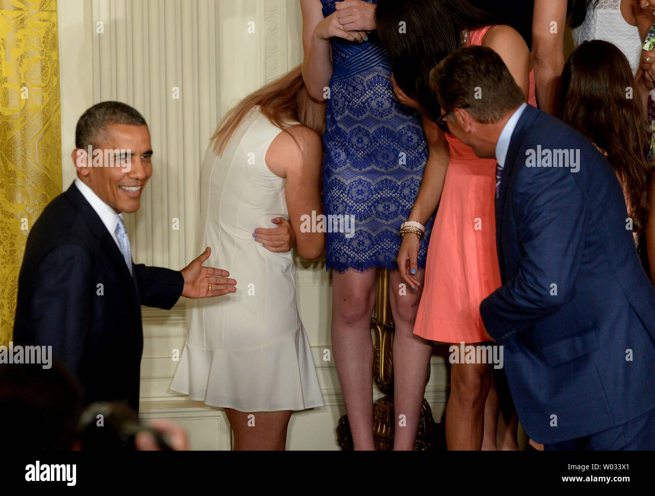 U.S. President Barack Obama smiles as he see that University of Connecticut star basketball player Stefanie Dolson (white dress) is all right but embarrassed after she slipped off the podium riser while Obama was shaking hands with head coachGeno Auriemma (R) during a presentation in the East Room of the White House in Washington, DC on June 9, 2014.  Obama honored both the women's and men's basketball teams from the University of Connecticut as they both won the NCAA collegiate basketball championships for the 2013-2014 season.    UPI/Pat Benic - Stock Image