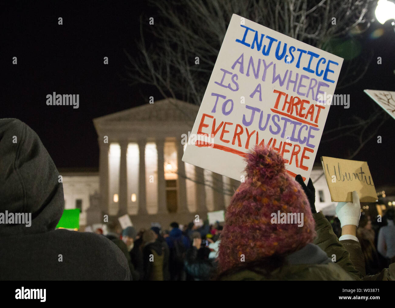 A protester holds up a sign in front of the U.S. Supreme Court to call on U.S. President Trump to reverse his administration's recent anti-refugee and anti-immigrant executive orders that bar for 90 days people traveling from Iraq, Iran, Sudan Syria, Yemen, Libya and Somalia to the United States in Washington DC on January 30, 2017. President Trump's executive orders additionally suspend processed refugee admissions for Syrians for 120 days and any new refugee applications and admissions for Syrian refugees to be banned indefinitely. Photo by Erin Schaff/UPI - Stock Image